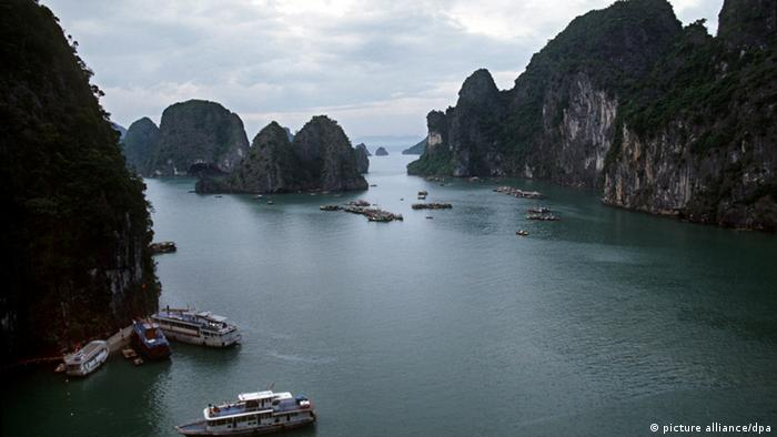 Mar com alguns barcos envoltos por altos rochedos