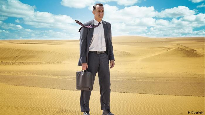 Film still from A Hologram for the King with Tom Hanks wearing a suit and holding a briefcase in the desert