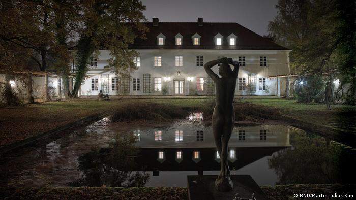 Pullach BND-Zentrale Präsidentenvilla, beleuchtete Villa hinter einem Teich in der Dunkelheit