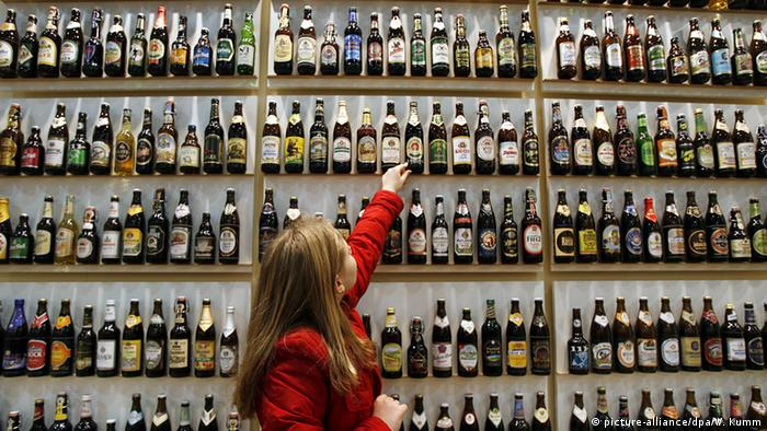 Germany, a woman in front of a shop selves filled with bottled beer in Berlin