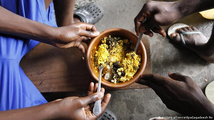 Two Liberians eating rice out of a bowl