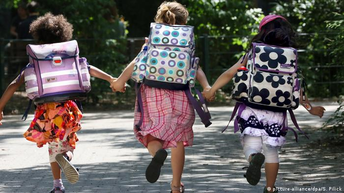 Three Little Girls with School bags, skipping away Copyright: picture-alliance/dpa/S. Pilick