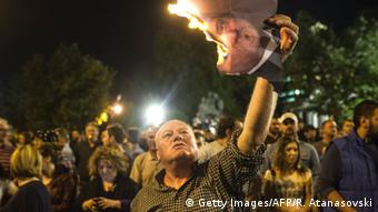 A protester holds up a burning photo of Macedonian President Ivanov, the flame having devoured half the picture.