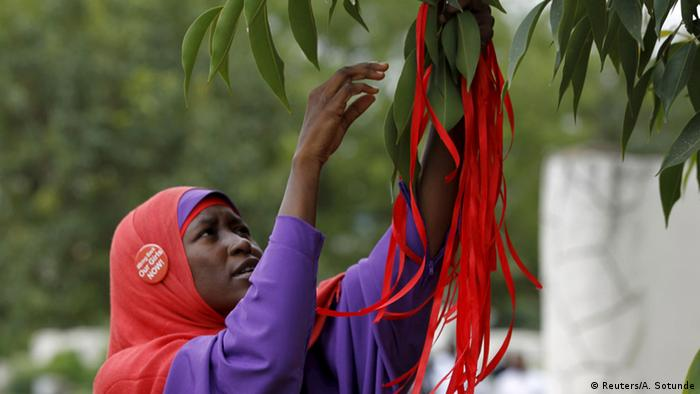 A girl ties red ribbons around a plant to mark the second anniversary of the kidnapping of the Chibok girls.