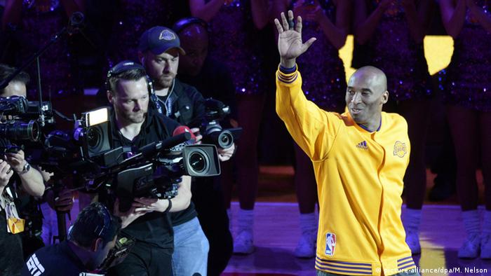 Kobe Bryant waves to fans ahead of his final game