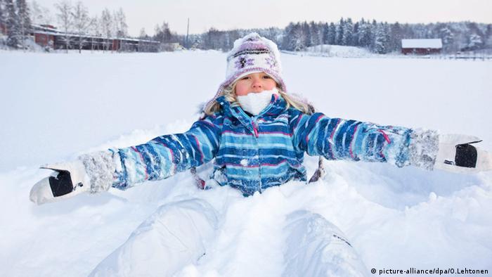 Kind spielt im Schnee Finnland