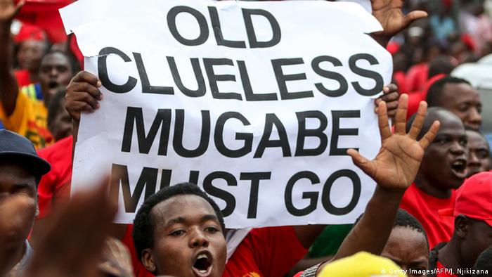 Protesters hold up a sign saying Old clueless Mugabe must go