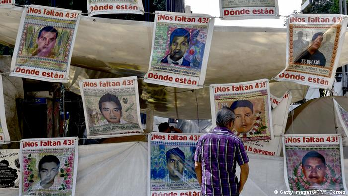 A pedestrian watches placards with portraits of some of the 43 missing students copyright: Getty Images/AFP/Y. Cortez