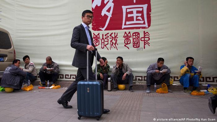 China Arbeiter im Anzug vor Bauarbeitern (picture-alliance/AP Photo/Ng Han Guan)