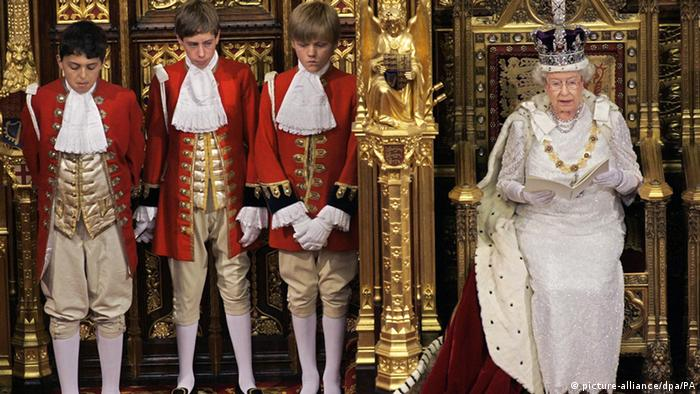 Queen Elizabeth II sits on her throne while wearing her crown with boys standing nearby
