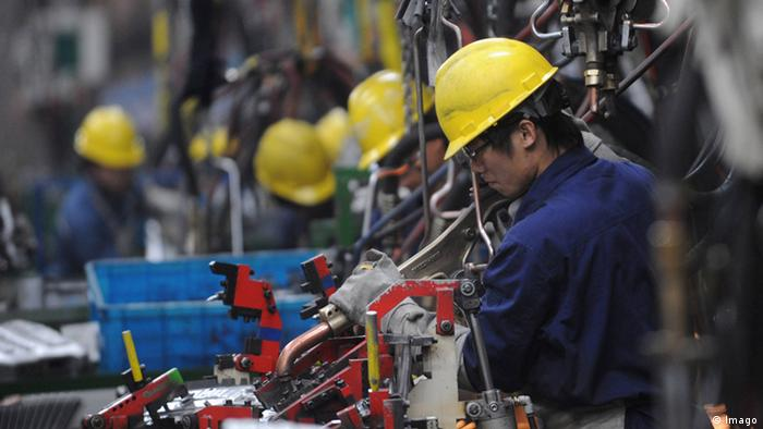 Chinese industry - workers in hard hats on a car assembly line