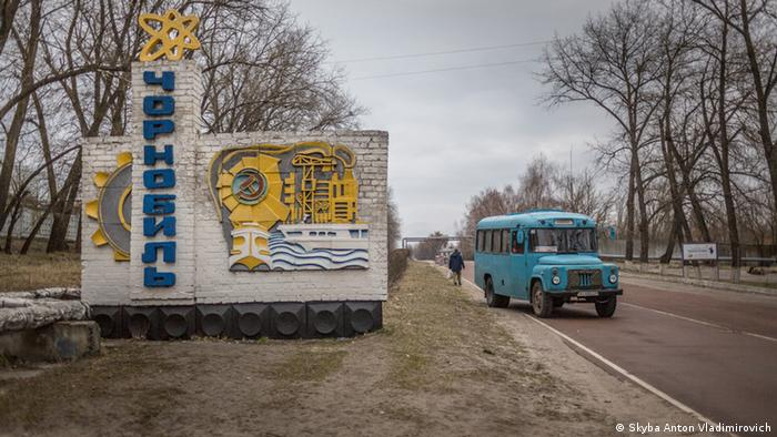 Автобус возле знака. указывающего въезд в город Чернобыль