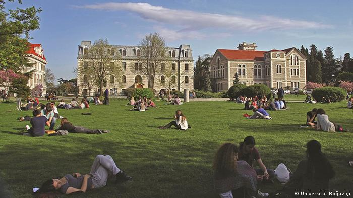 Students sit on the grass in front of university buildings