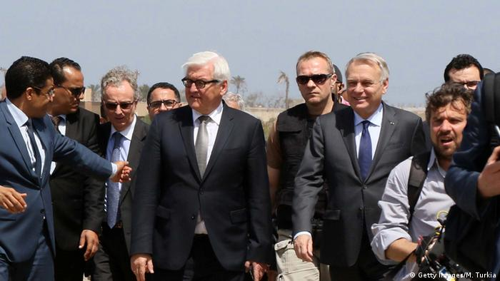 French Foreign affairs minister Jean-Marc Ayrault (C-L) and German Foreign Minister Frank-Walter Steinmeier (C-R) walk on the tarmac upon their arrival in the Libyan capital, Tripoli on April 16, 2016