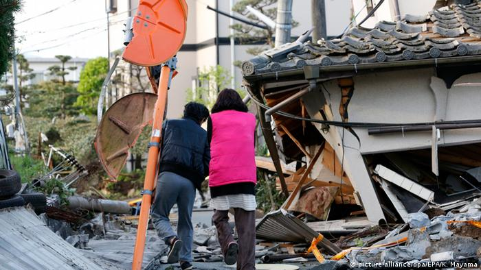 Residents walks through debris of collapsed houses in Mashiki Copyright: picture-alliance/dpa/EPA/K. Mayama