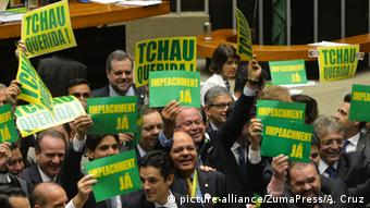 Parliamentarians hold up pro-impeachment signs.