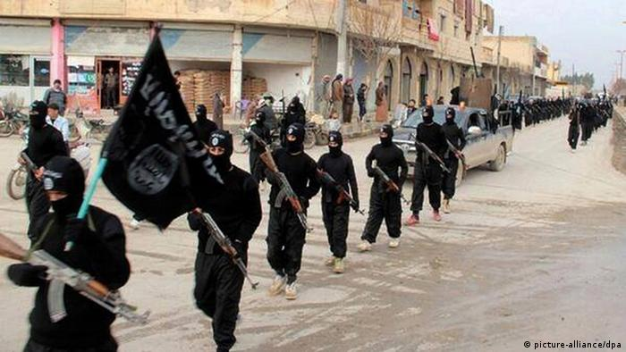 IS militants, dressed in black and carrying automatic rifles, march through Raqqa, Syria, their self-proclaimed capital.