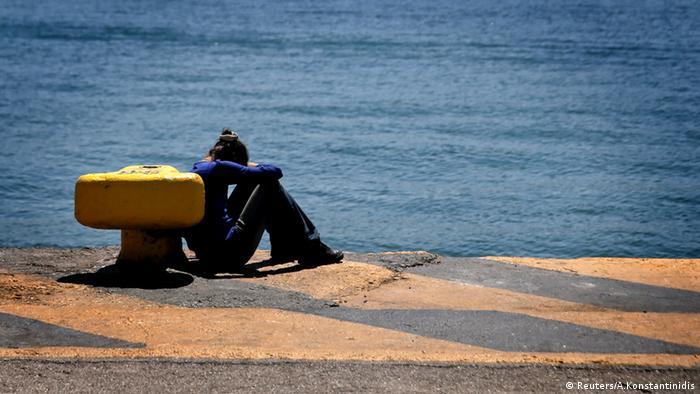 Frau sitzt im Hafen von Piräus an einer Anlegestelle