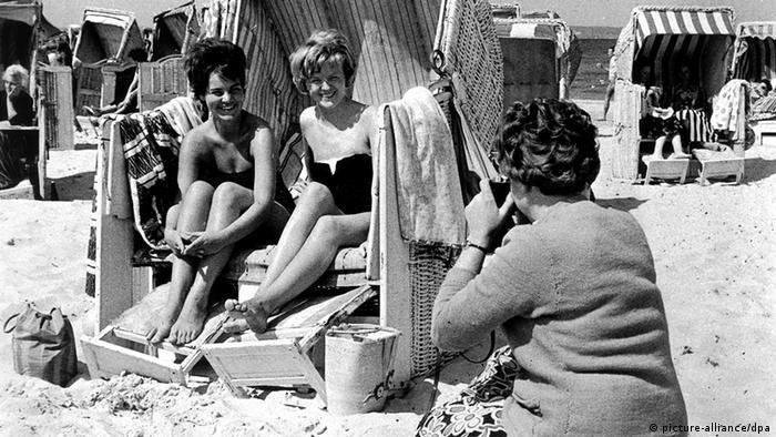 Ein Schwarz-Weiß-Foto aus den 1960er Jahren: Im Vordergrund hockt eine Frau und fotografiert zwei junge Frau, die in einem Strandkorb auf Rügen sitzen.