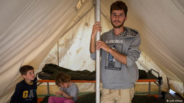 Kemal Shamo stands in a tent