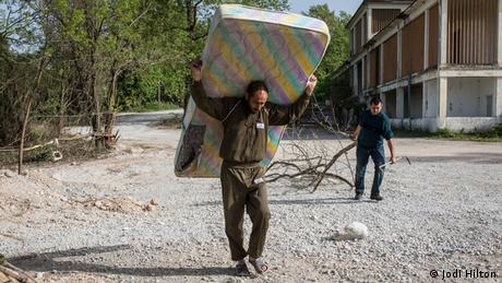 A man carries a mattress on his back