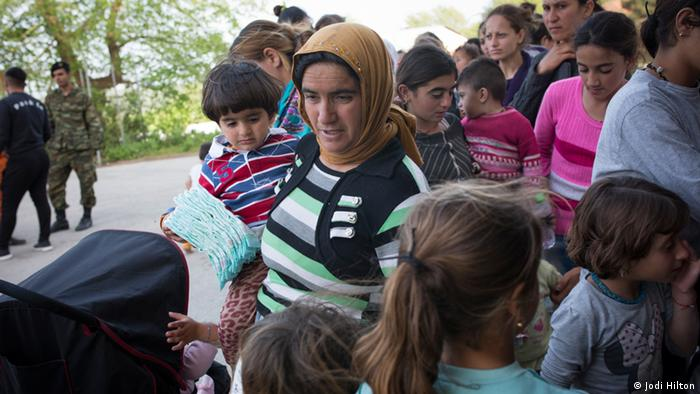Women and children stand in line to collect supplies