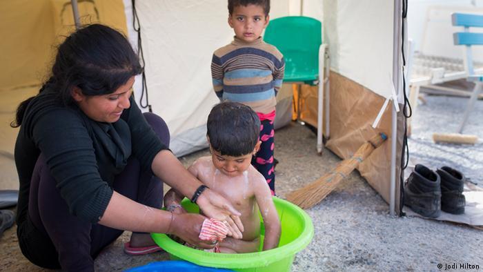 A girl bathes a small boy in a bucket
