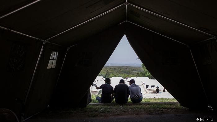 Men sit in the shade a tent
