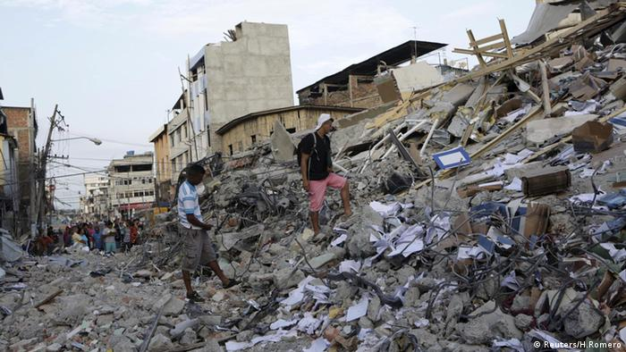 Survivors walk on a mountain of rubble and debris that was once a hotel in Portoviejo.