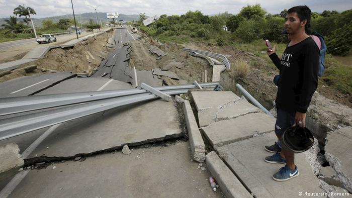 A resident stands on a collapsed bridge after an earthquake struck off the Pacific coast, in Portoviejo, Ecuador, April 18