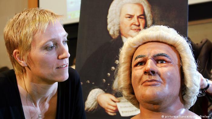Une femme contemple un mannequin à perruque, avec Bach