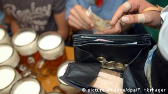 ein Kelnner hält eine geöffnete Geldtasche in der Hand. Im Hintergrund stehen zwei Glas Bier und ein Mann will bezahlen.