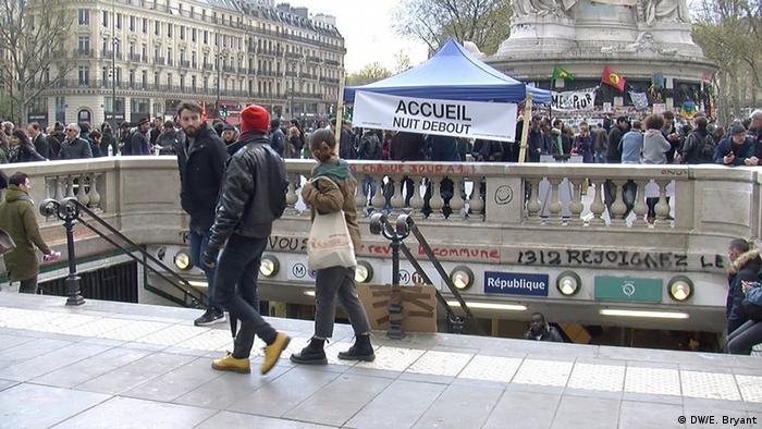 People walk past the underground station at Place de la Republique