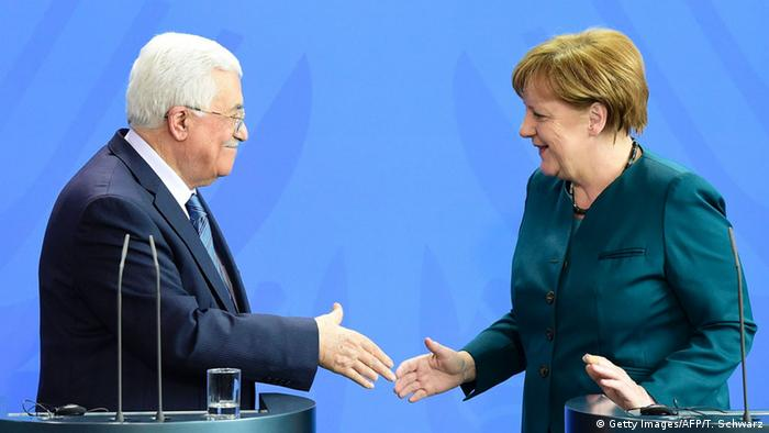 Palestinian president Mahmoud Abbas and German Chancellor Angela Merkel shake hands after a press conference