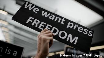 A hand holds up a sign that reads, we want press freedom.