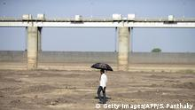 01.04.2016 **** An Indian man holds an umbrella as he walks on the dry reservoir bed next to Gunda Dam by Gunda village in Botad district, some 150 km from Ahmedabad in India's western Gujarat state, on April 1, 2016. Vast regions of western India have been facing acute water shortages due to drought conditions. / AFP / SAM PANTHAKY (Photo credit should read SAM PANTHAKY/AFP/Getty Images) © Getty Images/AFP/S. Panthaky