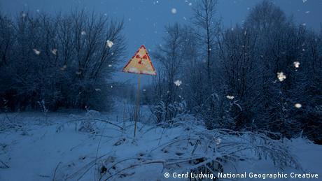 Ein Warnschild in abendlicher, schneebedeckter Landschaft - Achtung radioaktive Strahlung! Foto: Gerd Ludwig, Nataional Geographic Creative
