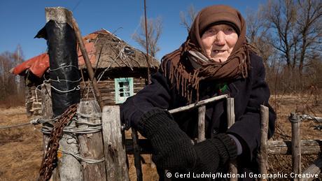 Die 92-jährige Kharytina ist in ihren Geburtsort innerhalb der Sperrzone zurückgekehrt. Sie steht vor ihrem Holzhaus.Foto: Gerd Ludwig, National Geographic Creative