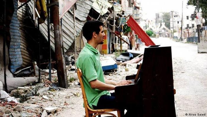 Aeham Ahmad playing the piano in Yarmouk (Niraz Saied)