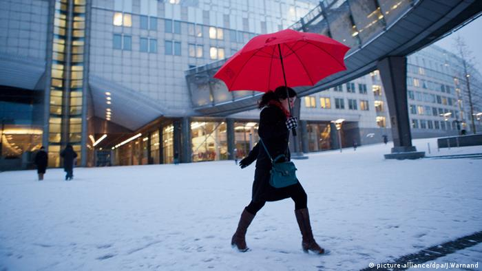 A woman walks in the snow in front of the European Parliament headquarters in Brussels,