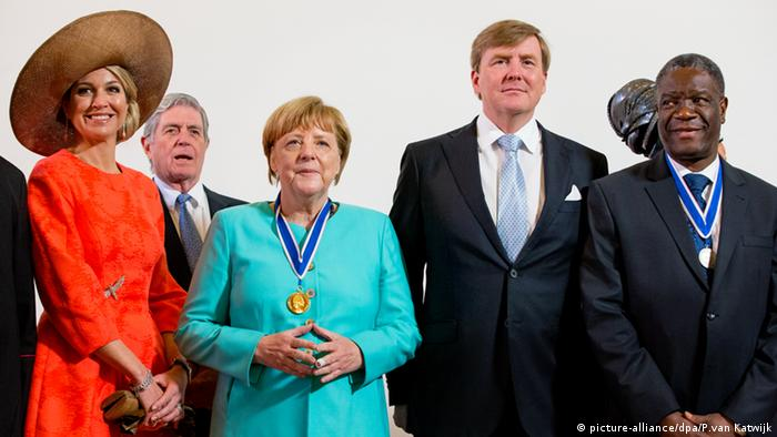 Denis Mukwege standing next to Dutch King and Queen and Germany's Chancellor Angela Merkel