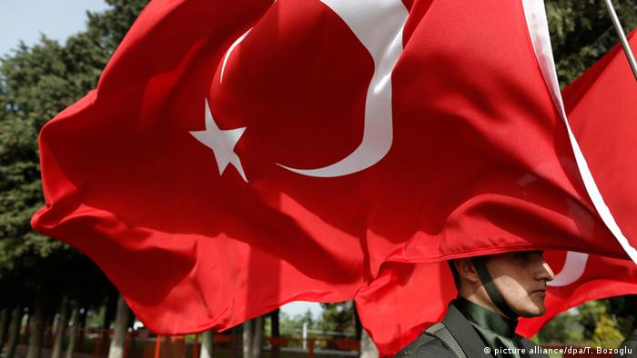 A Turkish flag with a soldier underneath it