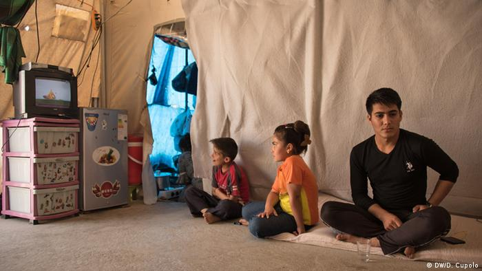 Saleem Alyas sits with relatives watching TV inside his tent in Sharya Refugee Camp