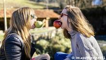 Two playful young women eating apples outside model released Symbolfoto PUBLICATIONxINxGERxSUIxAUTxHUNxONLY MGOF001510 Two playful Young Women Eating Apples outside Model released Symbolic image PUBLICATIONxINxGERxSUIxAUTxHUNxONLY MGOF001510 imago/Westend61