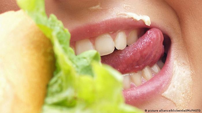 A close-up of a mouth biting into a hamburger