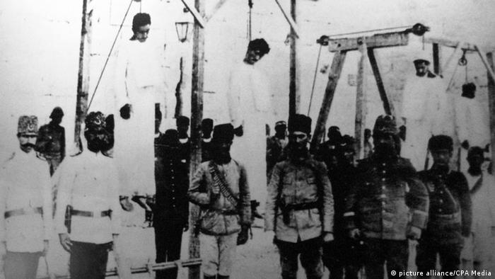 Турецкие солдаты стоят у виселиц с повешенными армянами