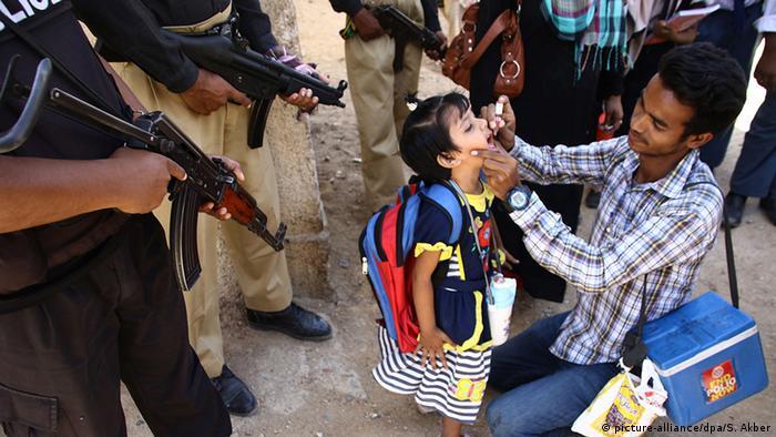 Police guard a polio vaccination team in Karachi