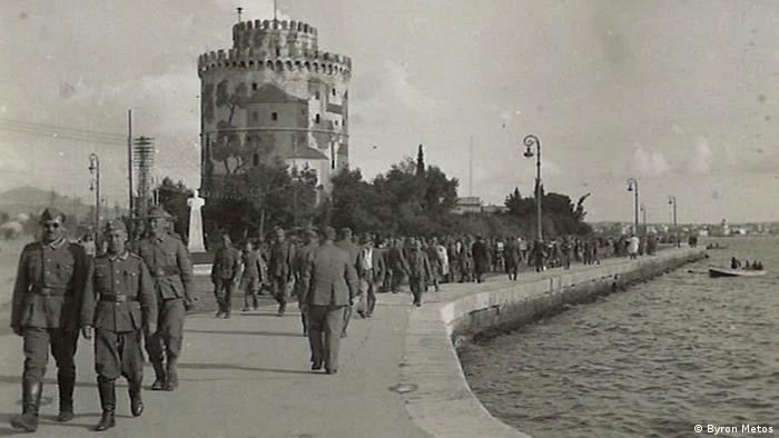 Soldiers walk along a pier in Thessaloniki in front of a tower (Byron Metos)