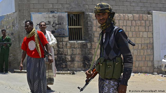 Yemeni plainclothes soldiers stand guard outside the headquarters of the security unit in the southern city of Mukalla