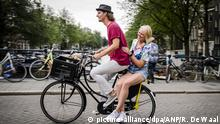ARCHIV 2015+++++Two people ride on a bicycle of Dutch bike rental company Yellow Bike that introduced the 'Yellow Backie' initiative, which transforms a bicycle luggage rack into an unofficial hitchhike seat in Amsterdam, The Netherlands, 13 August 2015. Fourty Amsterdam locals and volunteers have swapped their luggage racks for new, free, yellow ones. If a tourist sees a bicycle sporting one of the yellow racks on the street, they are invited to yell 'Backie!' to get a ride. The scheme enables visitors to receive a free tour of the city from a local and helps Amsterdammers connect with people from around the world. EPA/REMKO DE WAAL BG Bildergalerie zum Thema Amsterdam (c) picture-alliance/dpa/ANP/R. De Waal